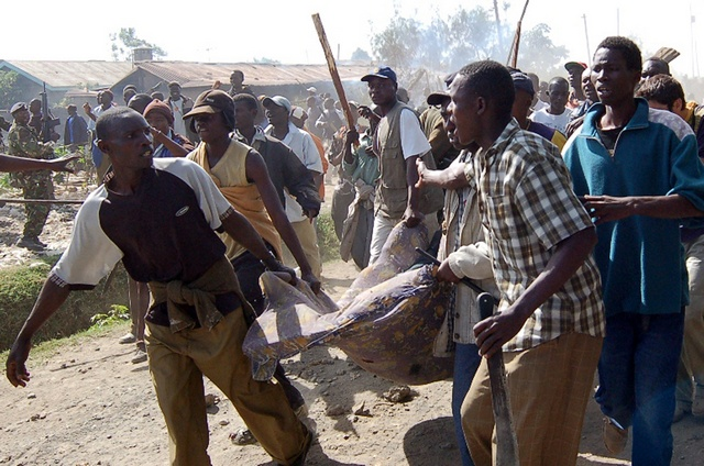 People carry the body of a man killed during ethnic clashes in Nakuru